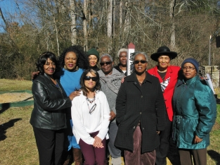A group of Rosenwald Alumni around the dedicated Peace Pole with Karesh (3rd from left.)